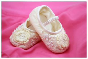 White ballet slipper styled baby booties with floral appliques, pink background