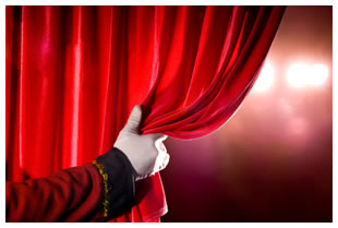 A white gloved hand pulling back a red theatre curtain