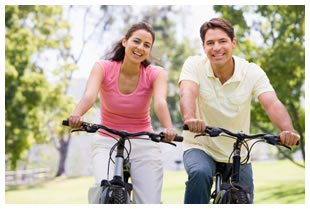 A woman and a man biking on a trail