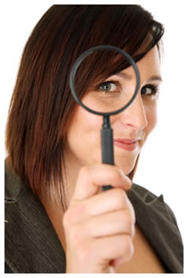 Female looking through a magnifying glass