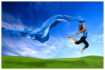 Woman running on the grass with a huge scarf trailing behind her