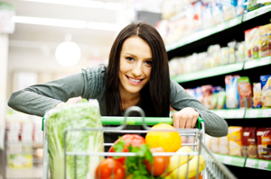 Young brunette shopping for groceries, veggies in her cart, smiling
