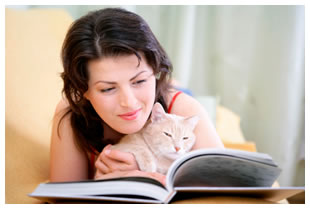 Woman holding a cat and reading a book
