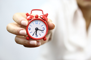 Female hand holding a miniature red alarm clock