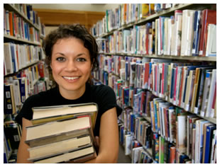 Woman smiling in the library with a bundle of books in her arms