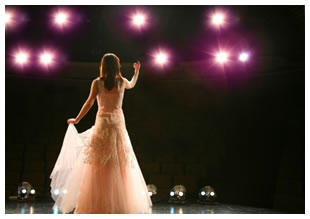 Woman singing on stage in a gown