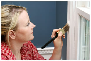 Woman painting the trim on a windowsill