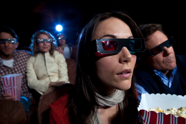 Woman viewing a movie in 3D, stereoscopic glasses, popcorn, theatre, other people