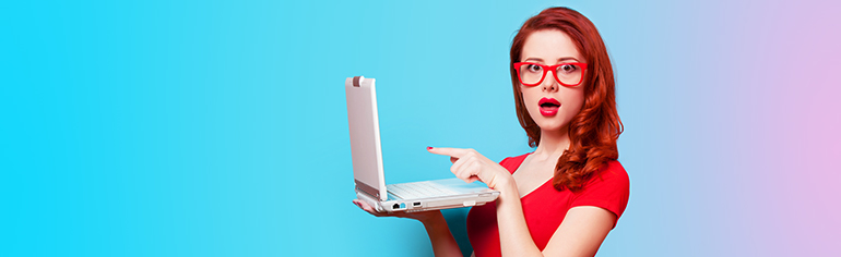 Woman dressed in red pointing at the screen of her laptop in surprise.