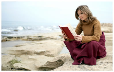A warmly dressed woman reading a book while sitting on the rocks on a cold and windy day at the beach.