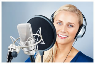 Woman recording with headphones on, standing behind a microphone and pop filter