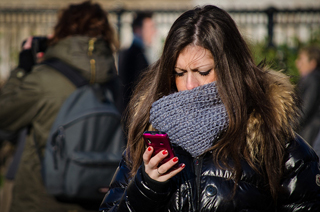 Woman wearing a warm scarf covering her mouth and nose, texting on a chilly day in Trafalgar Square.