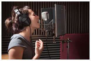 Woman singing into a microphone in a recording studio