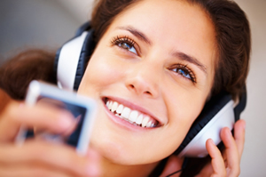 Woman smiling, listening to audiobook on an MP3 player