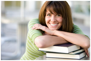 Woman smiling with arms resting on a book
