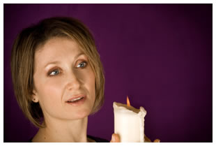 Woman holding a white candle, purple background