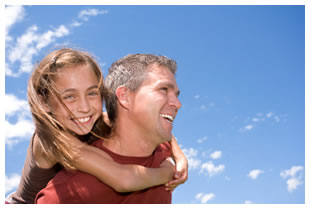 Young daughter with her daddy with a blue sky in the background