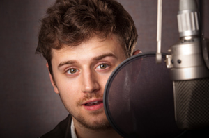 Young man standing behind a pop filter and microphone