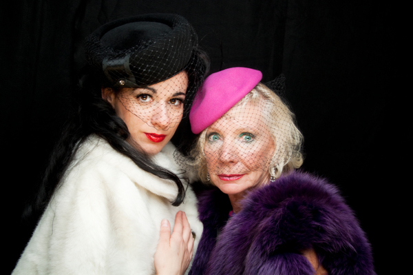 Young, brunette actress with hat on next to elderly blonde actress with hat on. Lace netting on faces. Fur coats.