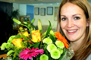 Young woman, smiling, holding a vibrant bouquet of flowers.